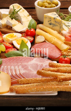 buffet of various types of cheese and appetizers set on rustic wooden board - Stock Photo