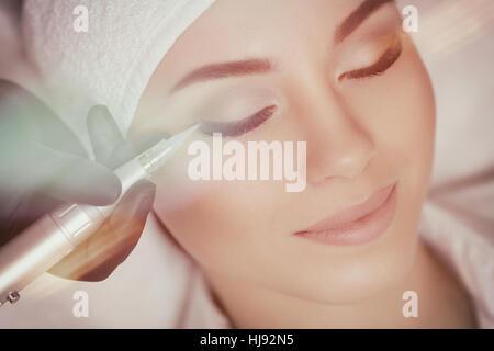 Cosmetologist making permanent make up at beauty salon - Stock Photo