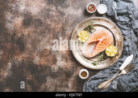 Fresh raw salmon steak, lemon, rosemary and spices on metal plate over dark rustic concrete background, top view - Stock Photo