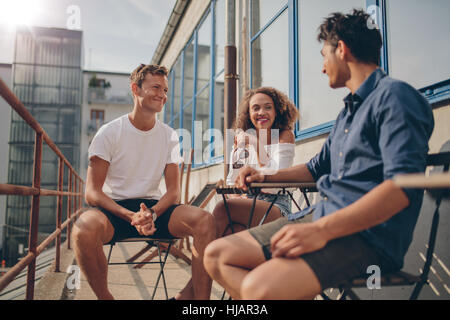 Three young friends together at outdoor cafe. Multiracial group of young people sitting around a small cafe table - Stock Photo