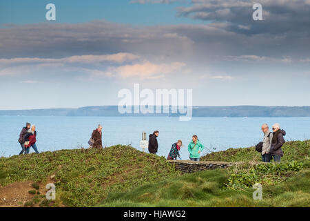 People walking. Tourists enjoy a stroll along the coastal path in Newquay, Cornwall. - Stock Photo