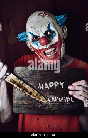 a scary evil clown pointing a big knife at a wore chopping board with the text happy carnival written in it - Stock Photo