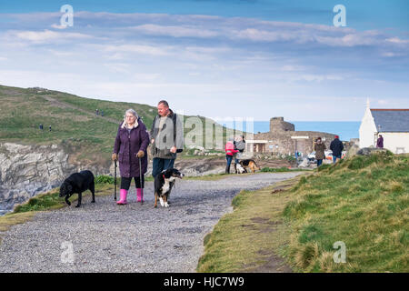 People and their dogs enjoy a stroll along the coastal footpath at Pentire Headland in Newquay, Cornwall, England. - Stock Photo