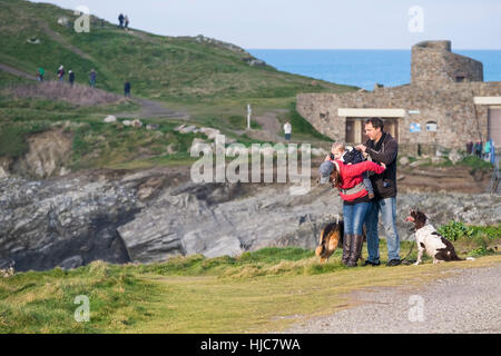 People and their dogs enjoying a stroll along the coastal footpath at Towan Headland in Newquay, Cornwall, England. - Stock Photo