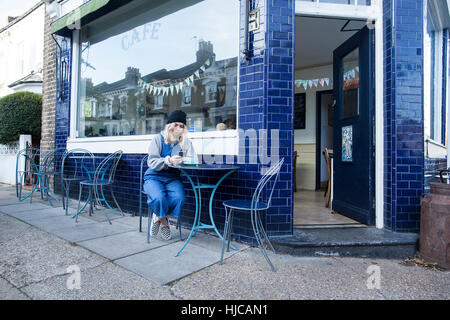 Young woman sitting outside cafe, using smartphone - Stock Photo