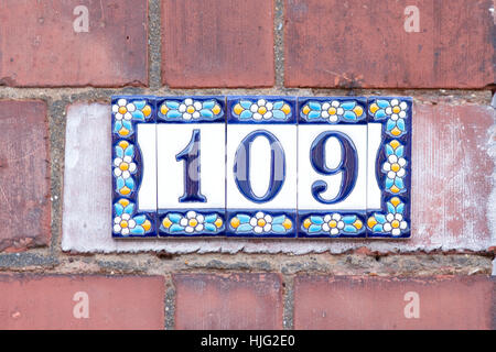 House number 109 sign on colourful flowery ceramic tiles - Stock Photo