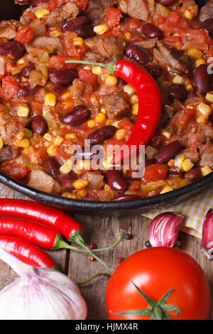 Mexican chili con carne close-up in a frying pan on a wooden background with the ingredients. vertical view from - Stock Photo