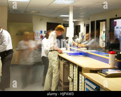 Hectic and very busy NHS hospital ward, with lots of actions as nurses and doctors are blurred in busy environment - Stock Photo
