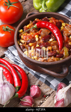Mexican food chili con carne in a pot and ingredients. vertical view from above - Stock Photo