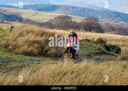 A man riding a dirt bike on a multi-use country track in Snowdonia National Park. Capel Curig, Conwy, Wales, UK, - Stock Photo