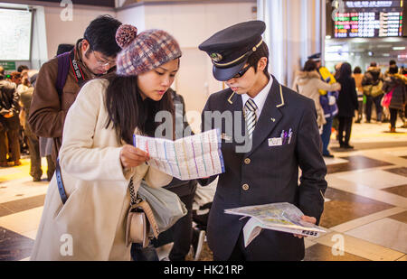 Tokyo Station,traveller speaking with a employee in main hall, Marunouchi, Tokyo, Japan - Stock Photo