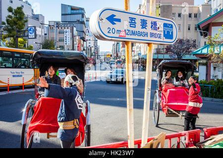 Tourists taking a Rickshaw ride, Asakusa, Tokyo, Japan - Stock Photo