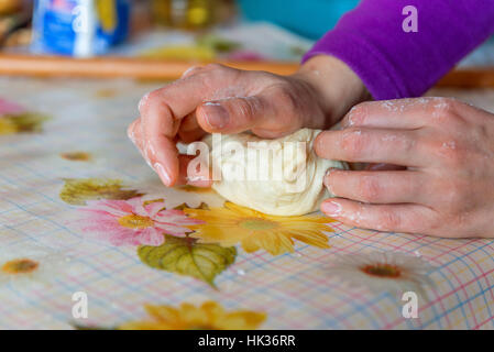 Woman hands kneading dough on the table at home - Stock Photo