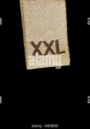 Macro XXL size clothing label, beige, brown, isolated vertical closeup - Stock Photo