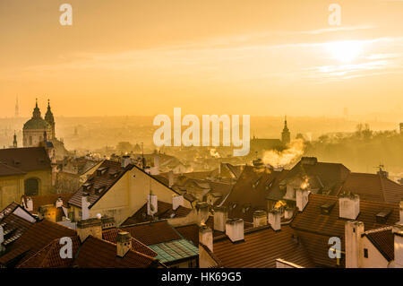 Morning atmosphere, roofs with smoking chimneys in fog, sunrise, historic centre, Prague, Bohemia, Czech Republic - Stock Photo