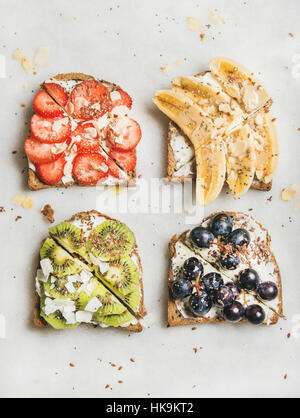 Healthy breakfast toasts. Wholegrain bread slices with cream cheese, various fruit, seeds and nuts. Top view, grey - Stock Photo