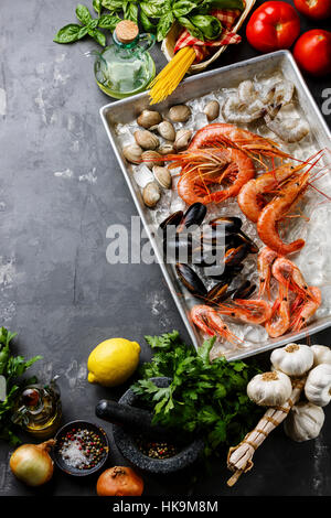 Raw fresh Seafood Cocktail with Clams and Shrimps and Ingredients for cooking pasta Spaghetti on concrete background - Stock Photo