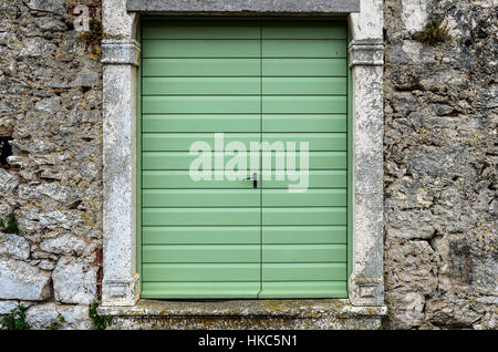 Old vintage green doors in a stone wall fence. Green panel door entrance to traditional courtyard on Silba Croatia. - Stock Photo