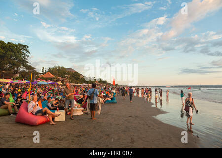 KUTA, INDONESIA - FEBRUARY 19, 2016: A large crowd of tourists, Indonesian and foreigners, enjoy the sunset at a - Stock Photo