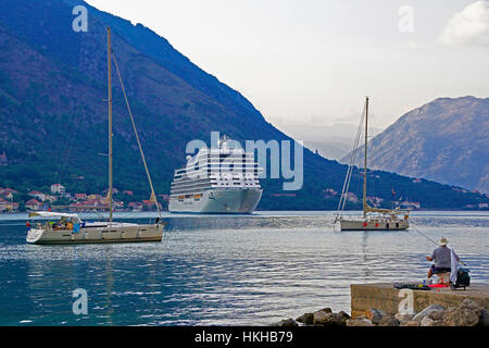Regent's Seven Seas Explorer luxury cruise ship with two sail boats and fisherman in harbor of Kotor. - Stock Photo