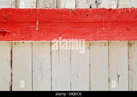 Horizontal red stripe of painted wooden board against white fence covered with cracked peeled old paint. Background - Stock Photo