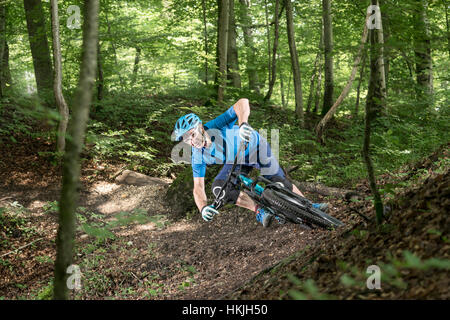 Mountain biker riding downhill in forest, Bavaria, Germany - Stock Photo