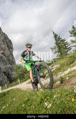 Mountain biker riding on uphill, Kampenwand, Bavaria, Germany - Stock Photo