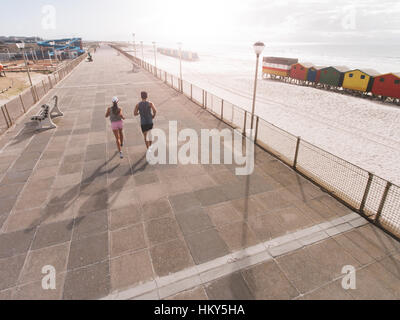 Rear view shot of young couple on morning run at beach promenade. Young man and woman jogging on road along the - Stock Photo