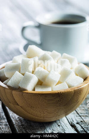 White sugar cubes in wooden bowl. - Stock Photo