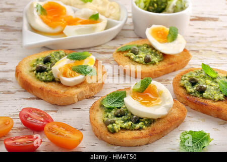 Fresh toasts with pesto and egg on wooden background on wooden background - Stock Photo