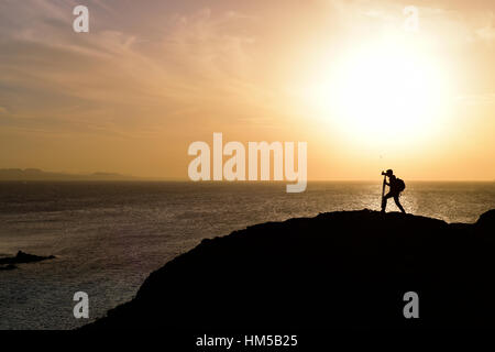 the silhouette of an unrecognizable young man taking a picture in front of the sea at dusk, against a colorful orange - Stock Photo
