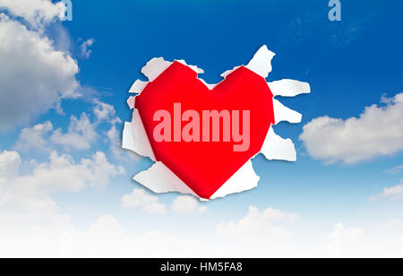 Heart shape hole through paper over blue sky - Stock Photo