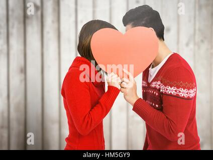 Couple kissing behind heart - Stock Photo