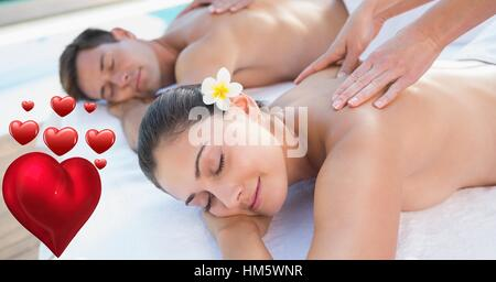 Masseur giving massage to couple at spa - Stock Photo