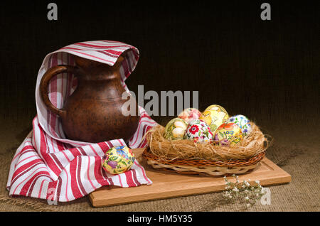 Decoupage Easter eggs in a basket and  jug under the towel. Selective focus. - Stock Photo