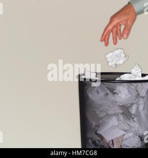 Man throwing paper balls into wastepaper basket - Stock Photo