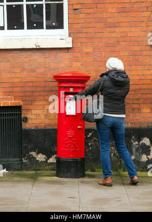 Woman posting a letter in a round red post box - Stock Photo