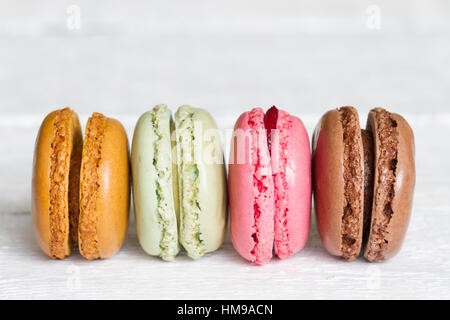 Colorful macarons, macaroons cake on white wooden background closeup - Stock Photo