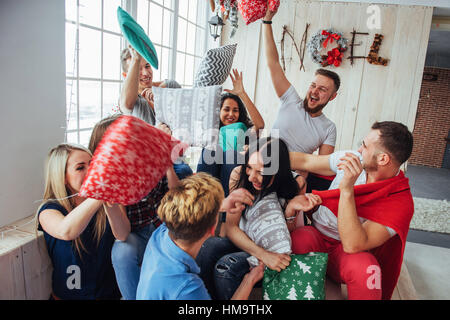Crazy young best friends fighting pillows at home. Mixed race group of people. Concept  entertainment and lifestyle - Stock Photo
