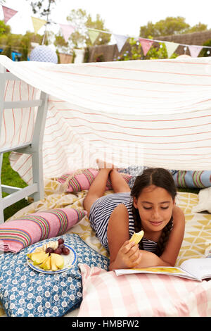 Girl Reading Book and Eating Snack In Home Made Garden Den - Stock Photo