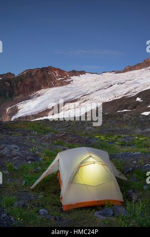Tent illuminated at dusk on climbers camp on slopes of Heliotrope Ridge, Mount Baker Wilderness North cascades Washington. - Stock Photo