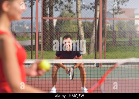 Young adult woman playing tennis and preparing for sports competition. Women against men. Healthy fitness concept - Stock Photo