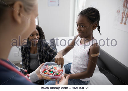 Female nurse offering girl patient candy in clinic examination room - Stock Photo