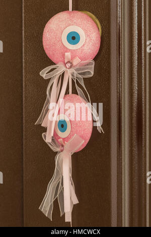 Pink evil eye hanging on the brown door. - Stock Photo