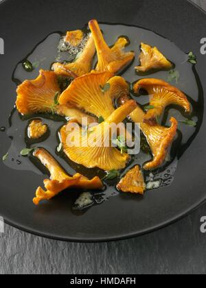 Wiild organic chanterelle or girolle Mushrooms (Cantharellus cibarius) or sauteed in butter and herbs. - Stock Photo