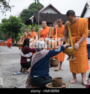 Monks and Donors, Early Morning Alms Procession, Luang Prabang, Laos - Stock Photo