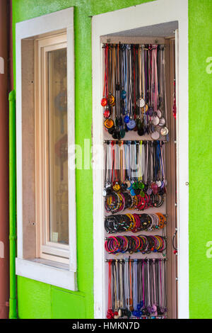 Bracelets and necklaces hanging on display in doorway at Burano, Venice, Italy in January - Stock Photo