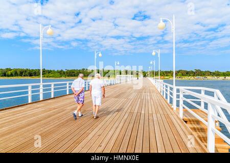 Couple of older men walking on wooden pier in Jurata town on coast of Baltic Sea, Poland - Stock Photo