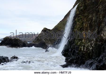 Trasaith Beach waterfall at high tide in winter Ceredigion Wales  Cymru UK GB - Stock Photo