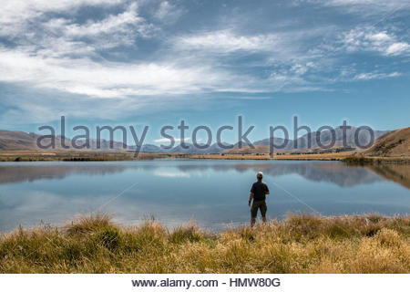 Man looks at Maori Lake at Hakatere Conservation Reserve, Canterbury, New Zealand - Stock Photo